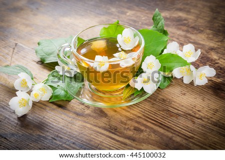 Herbal tea with jasmine flowers on old wooden table - stock photo