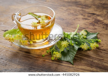 Herbal tea with linden flowers on old wooden table - stock photo