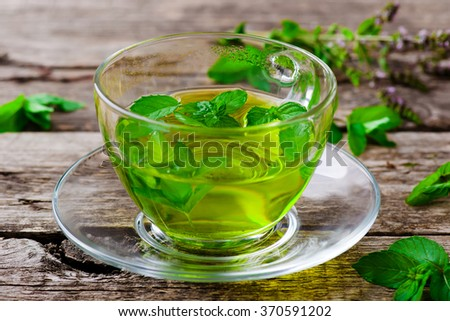 herbal tea with organic herbs in a glass cup on a wooden table. style rustic. selective focus - stock photo