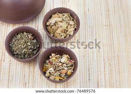 Herbal teas in small clay tea cups on a natural matting. - stock photo