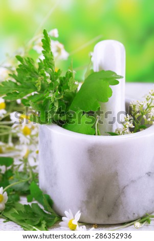 Herbs and flowers with mortar, on wooden table, on bright background