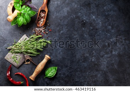 Herbs and spices cooking on stone table. Basil, rosemary, pepper and salt. Top view with copyspace