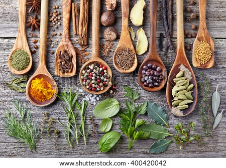 Herbs and spices on a wooden board - stock photo