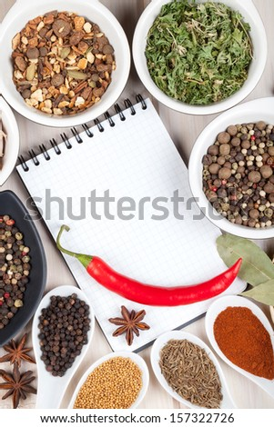 Herbs and spices on wood table background with blank notepad for copyspace