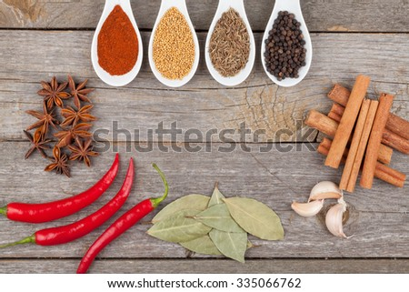 Herbs and spices on wood table background with copyspace - stock photo
