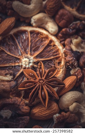 Herbs and spices with dramatic color grading. Focused on anise star.  Dried nuts, oranges and spices. - stock photo
