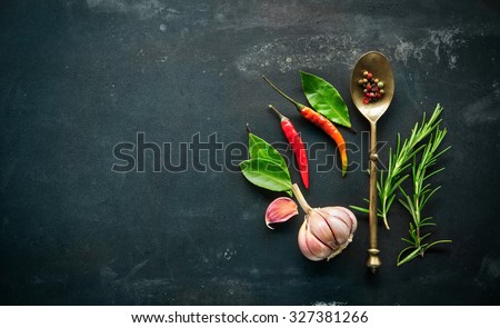 Herbs and spices with old metal spoon on slate background - stock photo