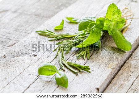 Herbs background - rosemary, basil, mint, rustic wood background, closeup