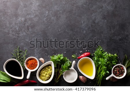 Herbs, condiments and spices on stone background. Olive oil and vinegar condiments. Mint, parsley and rosemary herbs. Salt, paprika and pepper spices. Top view with copy space - stock photo