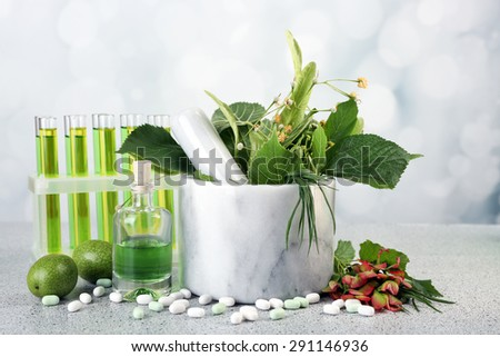 Herbs in mortar, test tubes and pills,  on table, on light background - stock photo