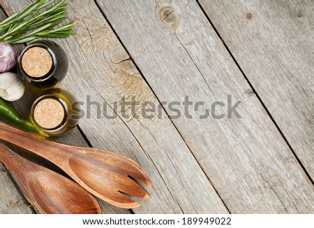 Herbs, spices and seasoning with utensils over wooden table background with copy space - stock photo