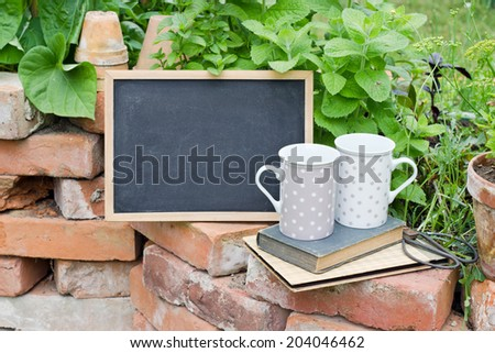 herbs with chalkboard, cup and books/herbs/garden - stock photo