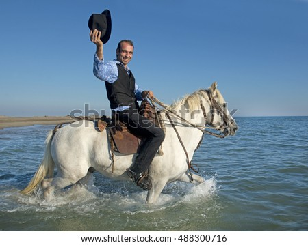 herdsman and Camargue walking in the sea