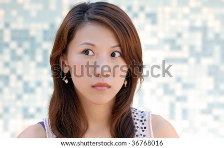 Here is a beautiful Asian lady in front of mosaic and watching. - stock photo