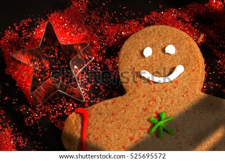 Here is a gingerbread man next to a Christmas cookie cutter.