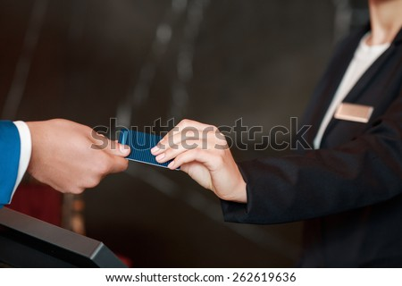 Here is a key. Closeup of a female receptionist hand and male businessman hand passing over a key to a hotel room