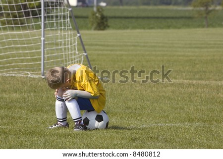 Here is a photo of a sad young boy sitting on a soccer ball.