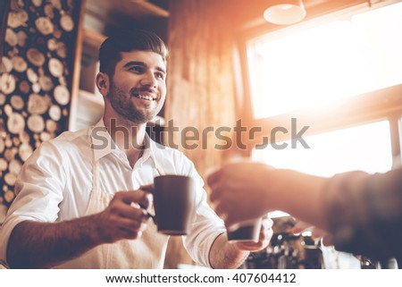 Here is your coffee! Close-up part of young handsome man in apron giving two coffee cups to his customer while standing at cafe - stock photo