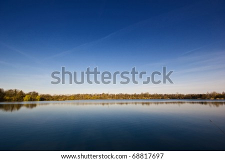 Here you can see a lake in the foreground and a big blue sky in the background. - stock photo
