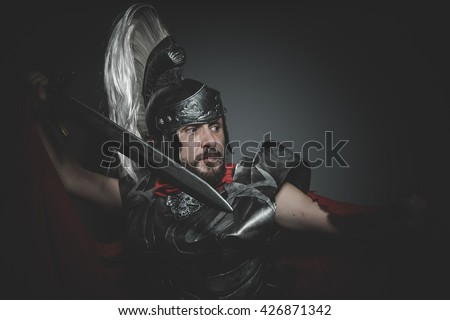 Hero, Praetorian Roman legionary and red cloak, armor and sword in war attitude - stock photo