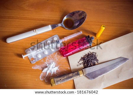heroin marijuana drugs syringe and spoon and lighters and candle knife - stock photo