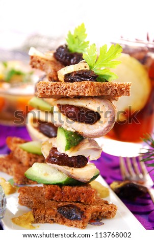 herring canapes with dark bread in star shape,prune and gherkin on christmas eve`s table - stock photo