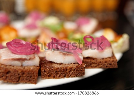 Herring canapes with marinated onion in plate, close-up, shallow focus - stock photo