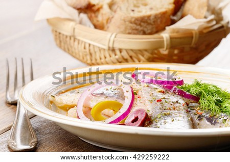 Herring fillets rustic style served with olives onions and dill