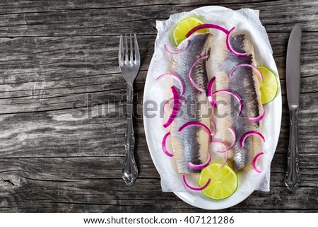 herring fillets with onion and lime slices on parchment paper on an oval dish on an old rustic table with a knife and fork, top view  - stock photo