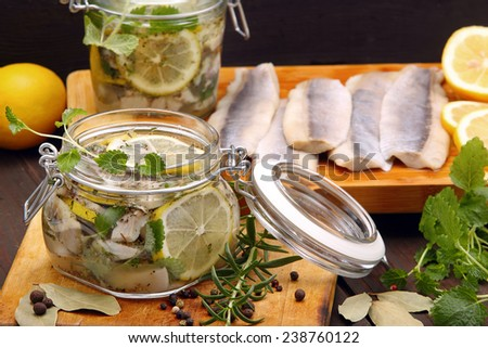 Herring marinated in oil with lemon and herbs - stock photo