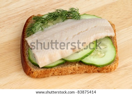 Herring on a piece of rye bread with cucumbers and dill - stock photo