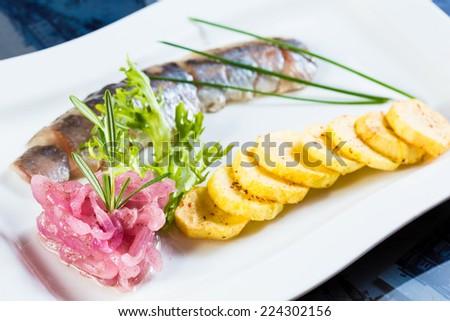 Herring with fried potatoes and red onions on a white plate - stock photo