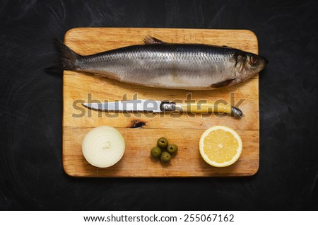 Herring with lemon and onions on a cutting Board - stock photo