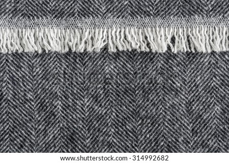 Herringbone wool tweed fabric background with closeup on textile texture and overlapping fringe edge - stock photo