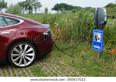Herwijnen, The Netherlands - July 24, 2015: Electric charging point at a public car park in Herwijnen. The charging station is on the right with the Tesla Model S is plugged in with a cable. - stock photo