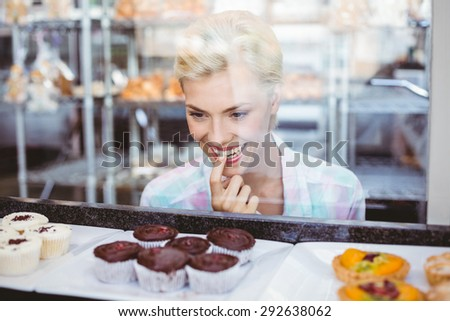 Hesitating pretty woman looking at cup cakes at the bakery - stock photo