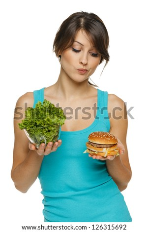 Hesitating woman making decision between healthy salad and fast food, over white background