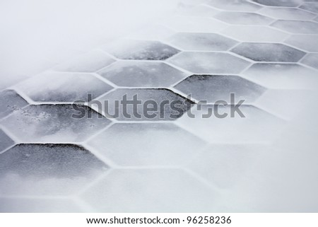Hexagonal sidewalk tiles covered with snow and ice - stock photo