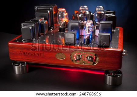 Hi end amplifier, with wood chassis and many electronic vacuum tubes : triode, rectifier, stabilizer, in a dark background - stock photo