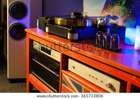Hi-end stereo system with turntable, preamplifier, power amplifier, phono amplifier, cd player on red wood stand with union jack - stock photo