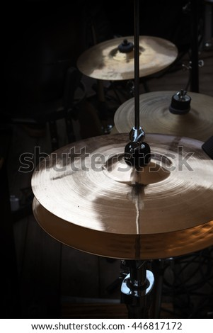 hi-hat and cymbals on stage, musical instruments in a percussion drum kit for modern  pop, rock, jazz, folk music and more, dark background, vertical, selected focus, narrow depth of field - stock photo