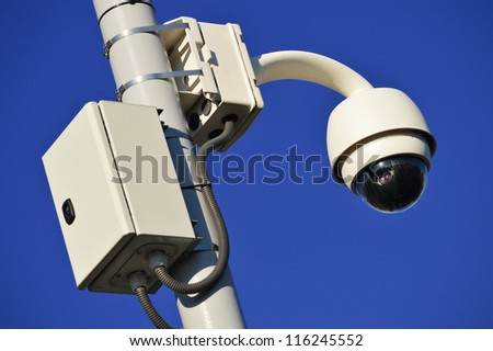 Hi-tech dome type camera over the blue sky - stock photo