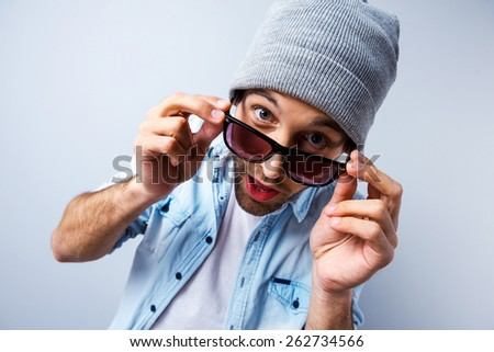Hi there! Top view of funny young man adjusting his sunglasses and looking at camera while standing against grey background - stock photo
