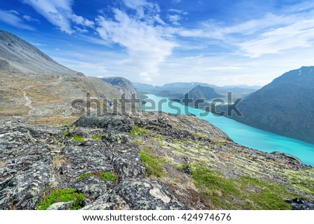 Hicker with blue backpack in mountains looking away - stock photo