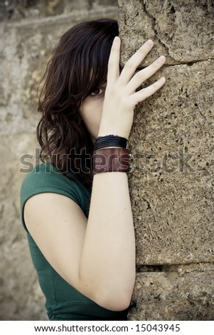 Hidden young woman behind stone wall - stock photo
