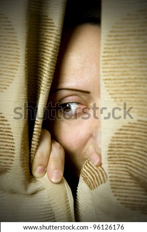 hide and seek, woman hiding behind curtains - stock photo