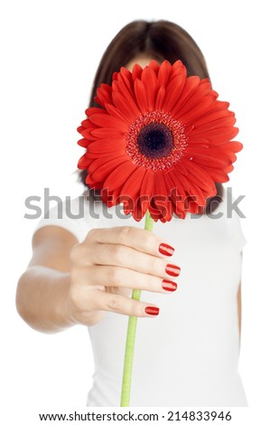 Hiding behind the gerber. Young woman holding a red gerber in front of her face while standing against pure white background. - stock photo