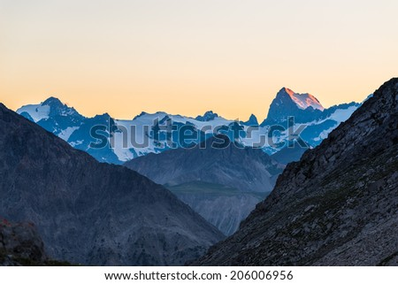 High altitude alpine landscape at dawn with first light glowing the majestic high peak of the Barre des Ecrins (4101 m), France. - stock photo