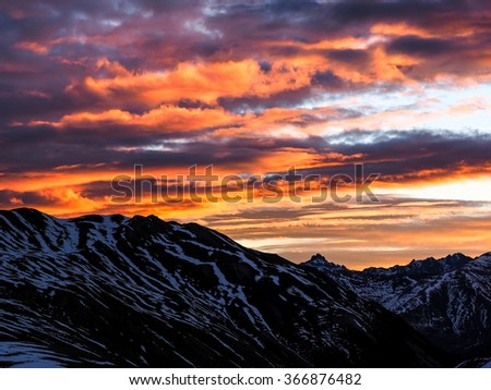 High altitude alpine valley at sunset in stormy weather. Location: western Alps, Torino Province, Italy.