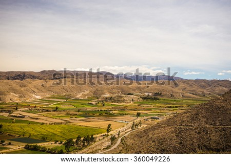 High altitude harsh barren landscape with scenic sky and volcanic cone in the distance. Wide angle view from above at 4000 m on the Andean highlands, Peru. - stock photo